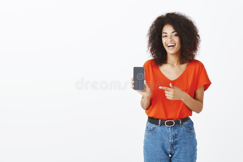 Najlepszy telefon dla niemądrej ceny kiedykolwiek Radosny ufny i zadowolony ciemnoskóry żeński mienia smartphone, śmia się i zdjęcie stock