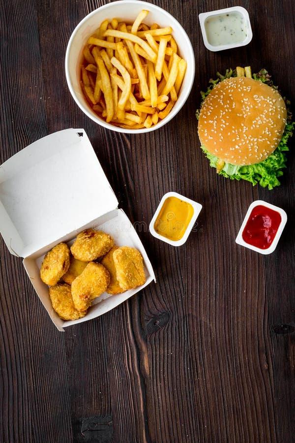 Najwięcej popularnego fasta food posiłku Chiken bryłki, hamburgery i francuscy dłoniaki na ciemnej drewnianej tło odgórnego widok obrazy royalty free