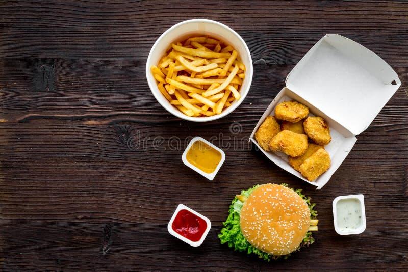 Najwięcej popularnego fasta food posiłku Chiken bryłki, hamburgery i francuscy dłoniaki na ciemnej drewnianej tło odgórnego widok zdjęcia royalty free