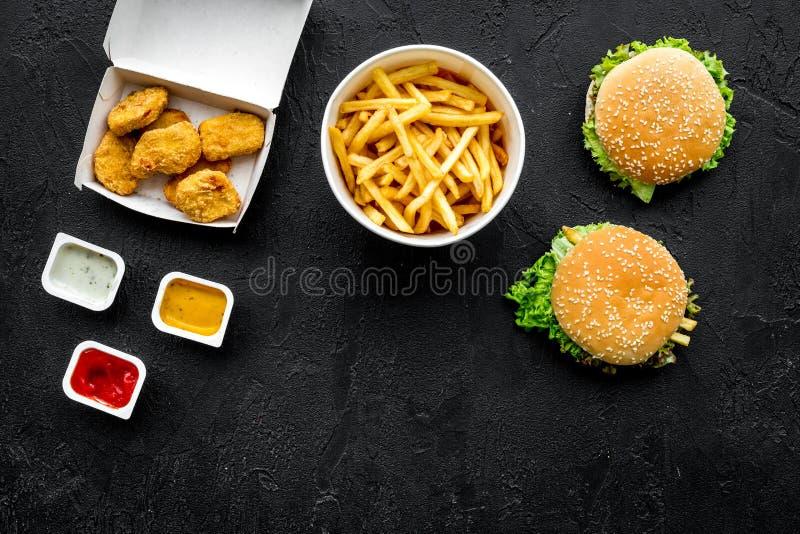 Najwięcej popularnego fasta food posiłku Chiken bryłki, hamburgery i francuscy dłoniaki na czarnej tło odgórnego widoku kopii prz fotografia stock