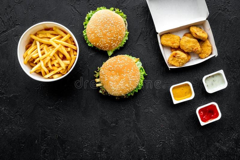Najwięcej popularnego fasta food posiłku Chiken bryłki, hamburgery i francuscy dłoniaki na czarnej tło odgórnego widoku kopii prz obraz stock