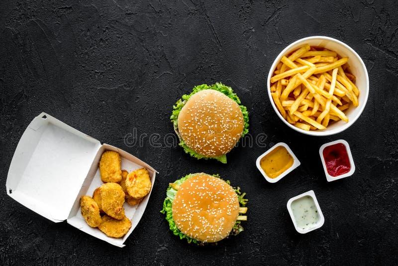 Najwięcej popularnego fasta food posiłku Chiken bryłki, hamburgery i francuscy dłoniaki na czarnej tło odgórnego widoku kopii prz obrazy royalty free