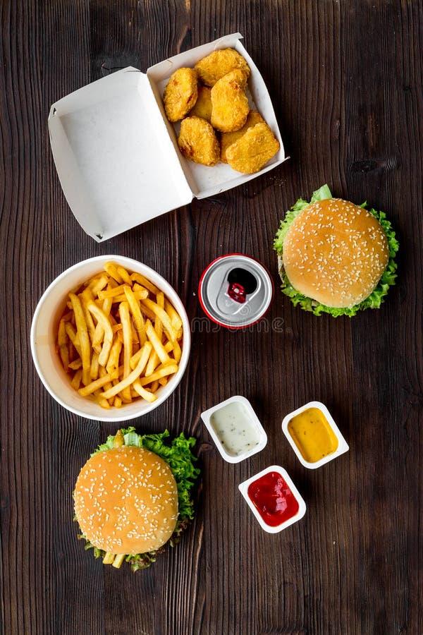 Najwięcej popularnego fasta food posiłku Chiken bryłki, hamburgery i francuzów dłoniaki na ciemnego drewnianego tła odgórnym wido zdjęcia royalty free