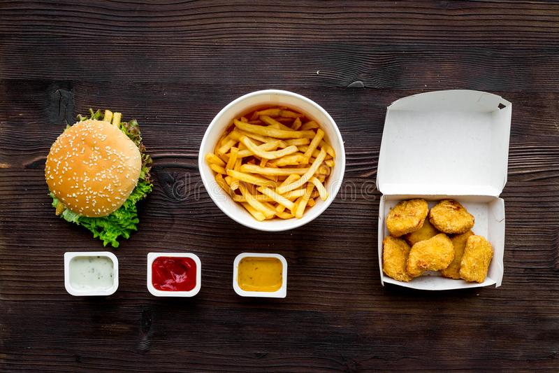 Najwięcej popularnego fasta food posiłku Chiken bryłki, hamburgery i francuzów dłoniaki na ciemnego drewnianego tła odgórnym wido fotografia royalty free