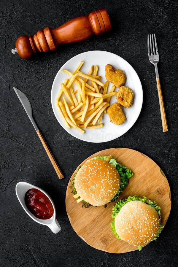 Najwięcej popularnego fasta food posiłku Chiken bryłki, hamburgery i francuzów dłoniaki na czarnego tła odgórnym widoku, obraz royalty free