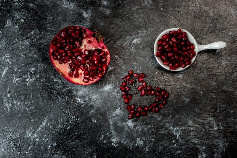 Najwięcej seducive owoc dla walentynka dnia - Kusicielski granatowiec, czerwieni ziarna układał w formie serca zdjęcie royalty free