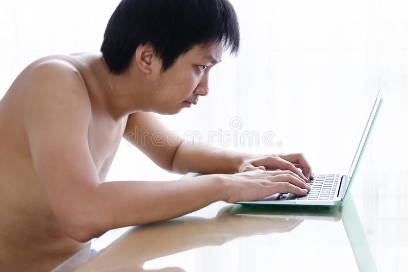 Naked Asian man stressed while working on laptop stock photo