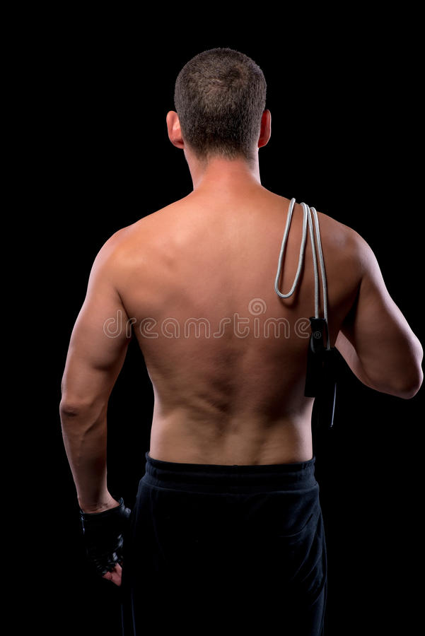 Naked back athlete with a skipping rope isolated. On a black background royalty free stock image