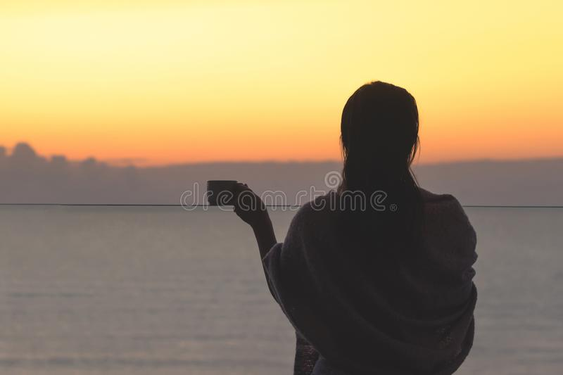Naked beautiful female with wet hair wrapped in a blanket with cup of coffee standing on the glass balcony early morning at sunris. E. Sea view royalty free stock images