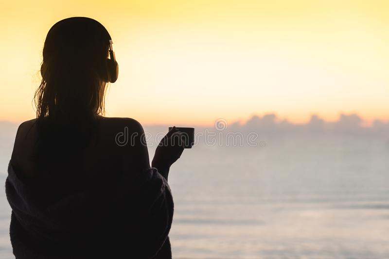 Naked beautiful female with wet hair wrapped in a blanket with cup of coffee standing on the glass balcony early morning at sunris. E. Sea view stock images