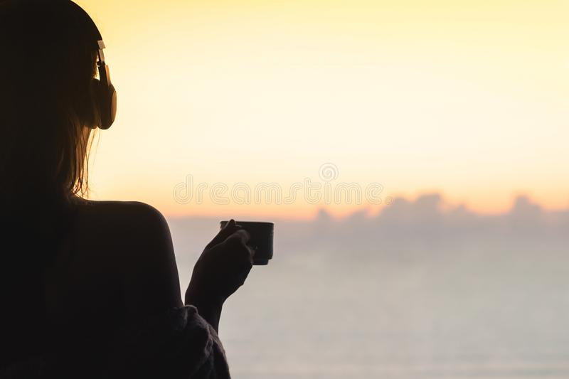 Naked beautiful female with wet hair wrapped in a blanket with cup of coffee standing on the glass balcony early morning at sunris. E. Sea view stock image