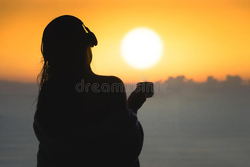 Naked beautiful female with wet hair wrapped in a blanket with cup of coffee standing on the glass balcony early morning at sunris. E stock image