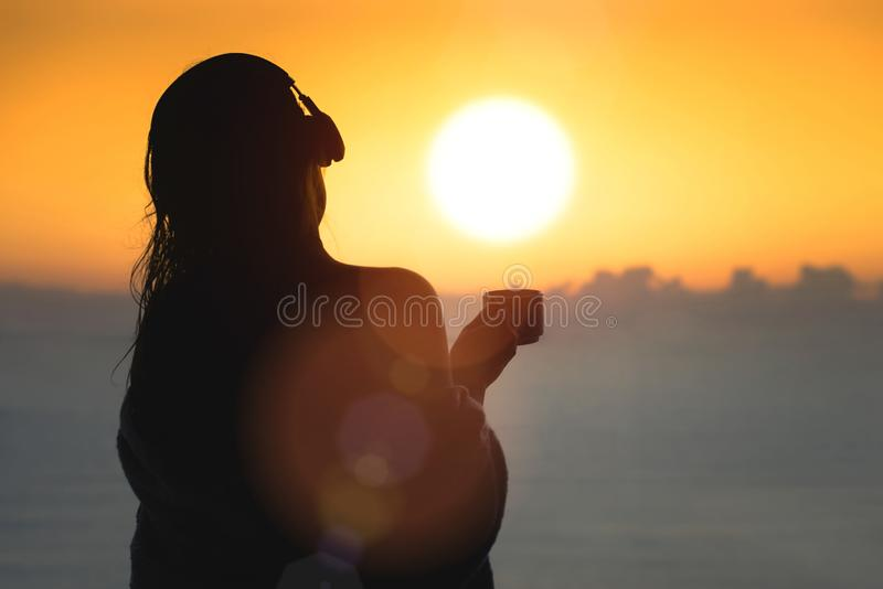 Naked beautiful female with wet hair wrapped in a blanket with cup of coffee standing on the glass balcony early morning at sunris. E. Sea view royalty free stock photo