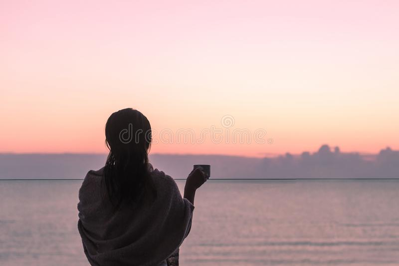 Naked beautiful female with wet hair wrapped in a blanket with cup of coffee standing on the glass balcony early morning at sunris. E. Sea view royalty free stock photography
