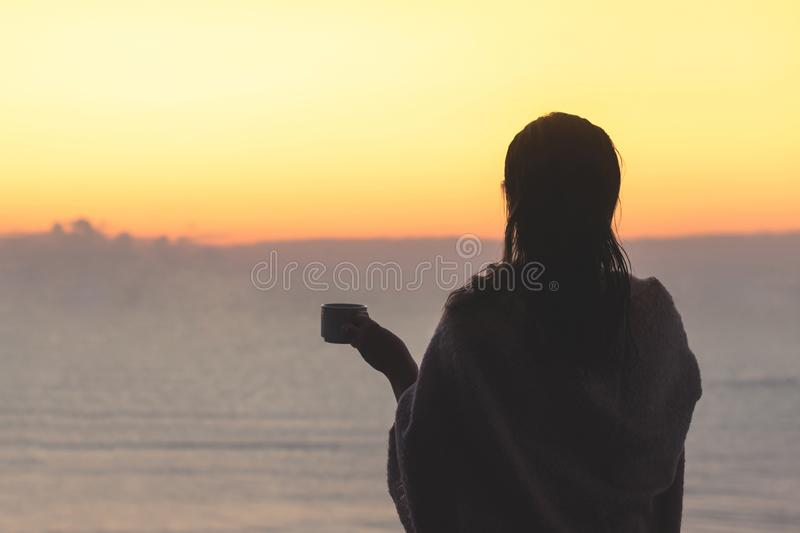 Naked beautiful female with wet hair wrapped in a blanket with cup of coffee standing on the glass balcony early morning at sunris. E. Sea view stock photos
