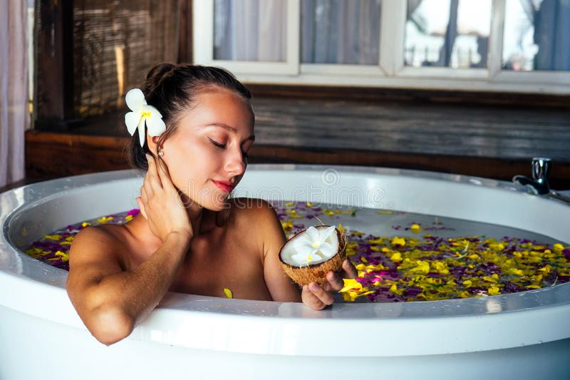 Naked brunette young woman relaxing in bath with petals in tropics. Time for yourself.romantic 14 february valentine day stock photo