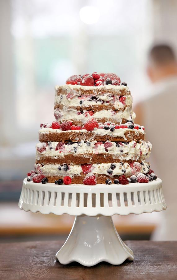 Naked cake with cream, decorated with strawberries, raspberries and blueberries, standing in a bakery.  stock image