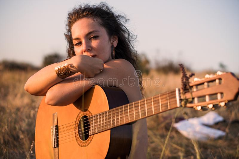 Naked Contemplative brunette girl Sitting with guitar in the field with taked off clothes on background stock image