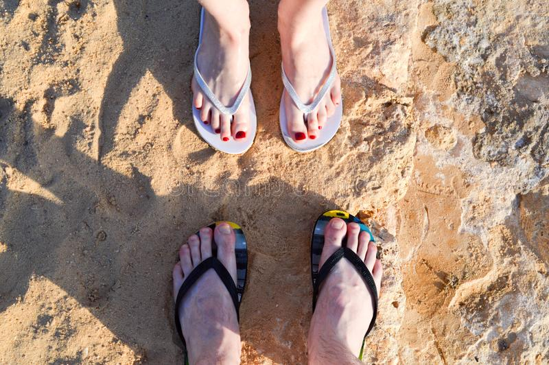 Female and male legs with fingers and nails with a red pedicure in flip flops against the background of yellow stones and sand. Naked female and male legs with royalty free stock photography