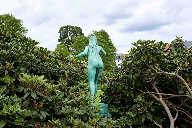 Naked girl bronze sculpture. Echo is a verdigrised bronze statue, by danish sculpture Aksel Hansen, of a young girl standing in the Kings garden in Copenhagen royalty free stock photo