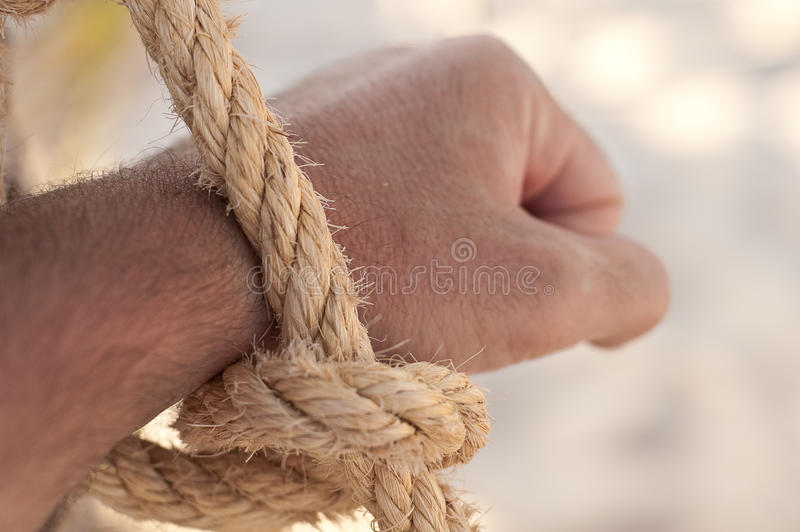 Naked hand tied. Single hand freeing itself by a rope loose stock photography