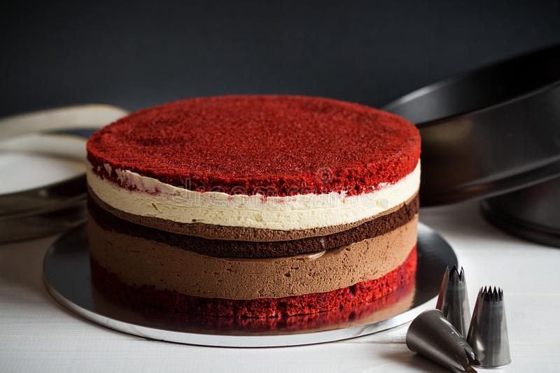 Naked layer cake with red velvet and chocolate biscuit and cream. Mousses on dark background with kitchen utensils royalty free stock photos