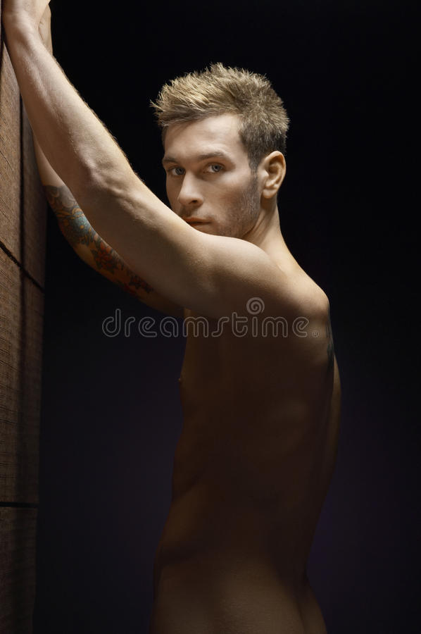 Naked Man Posing. Portrait of a naked man over black background stock image