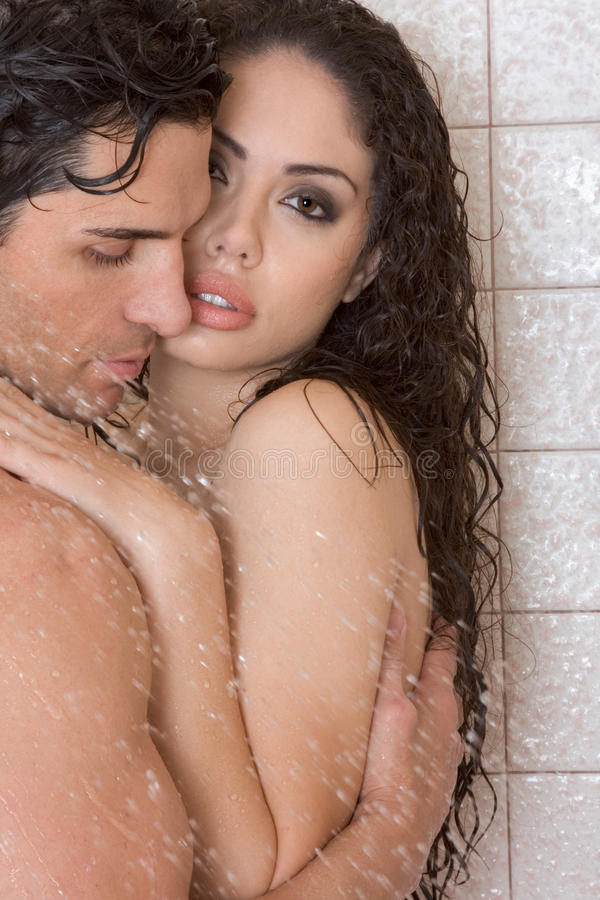 Naked Man and woman in love are kissing in shower. Loving affectionate nude young heterosexual couple in affectionate sensual kiss after taking shower. Mid adult royalty free stock photo