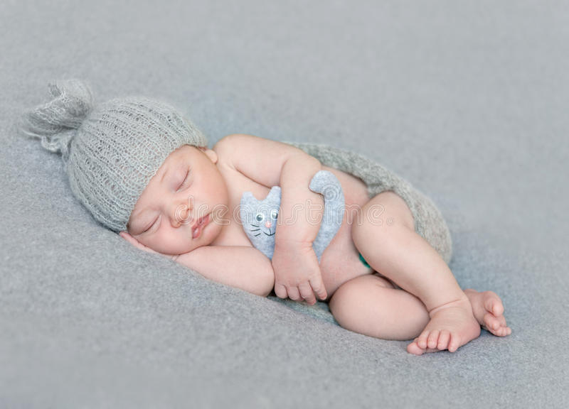 Naked newborn baby in gray hat with toy stock photography