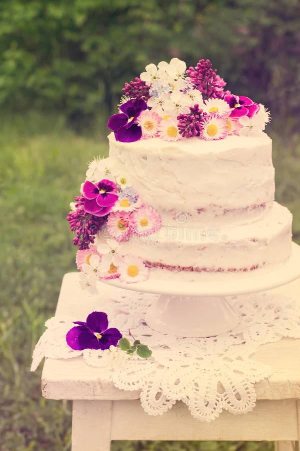 Naked wedding cake. Decorated with spring flowers, selective focus, toned royalty free stock image