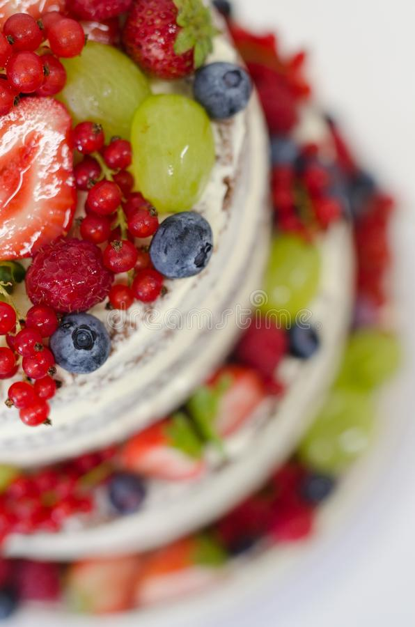 Naked cake with various fruits. Naked wedding cake with fresh fruits, strawberries, blueberries, red currant, grapes stock images