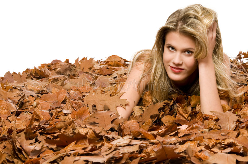 Naked woman surrounded by dried leaves stock photo