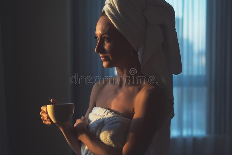 Naked woman with towel on her head and body drinking herbal tea after bath. Naked woman with towel on her head and body drinking herbal tea after bath royalty free stock images