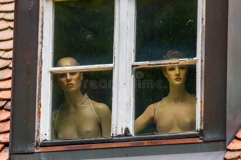 Naked women behind a window. Observing street life royalty free stock image