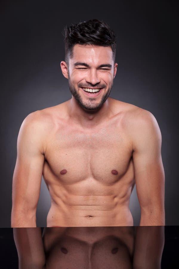 Naked young man laughs hard stock photo