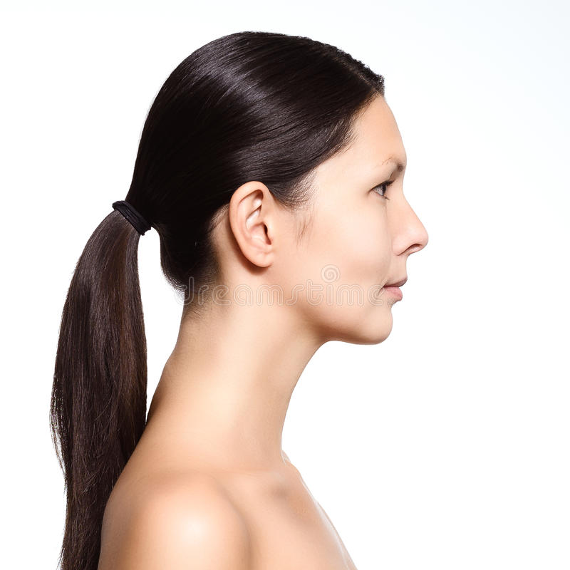Naked young woman standing in profile. Head and shoulders portrait of a naked young woman with a serious expression standing in profile with her long brown hair stock photos