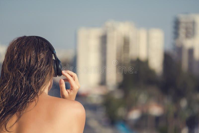 Naken härlig kvinna med vått hår i hörlurar på balkongen av hennes lägenhet mot bakgrunden av semesterortstaden arkivbild