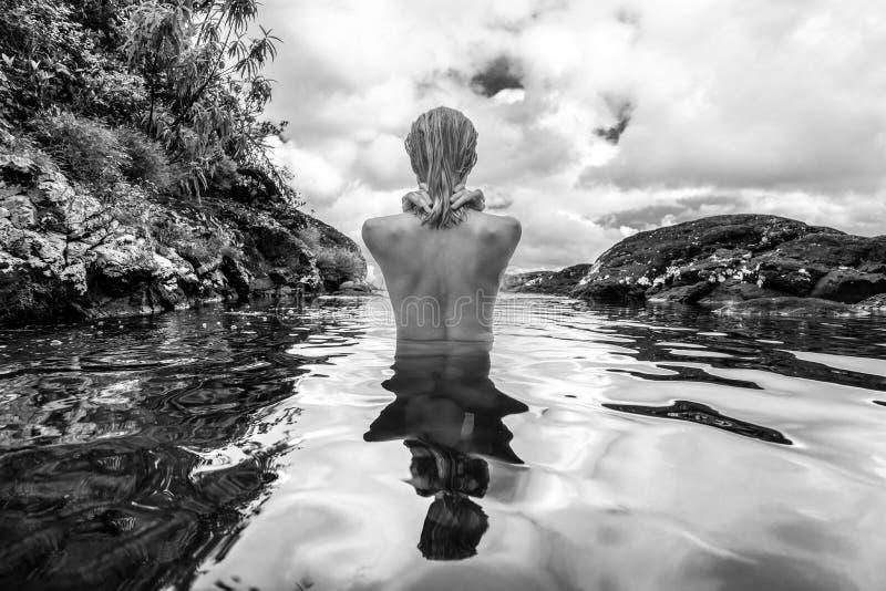 Naken kvinna som badar och kopplar av i naturlig simbass?ng i svartvitt arkivbilder