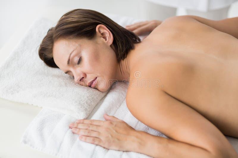 Naken kvinna som kopplar av i brunnsort royaltyfria foton