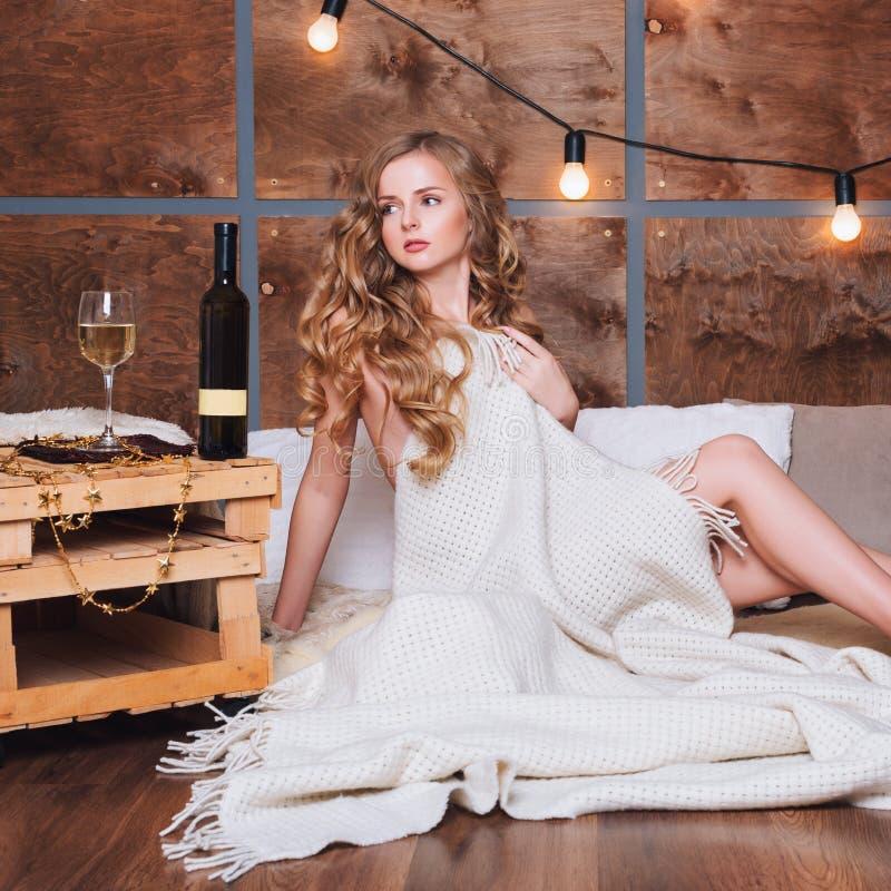 Naken kvinna som slås in i en filt med exponeringsglas av vitt vin Härlig blond flicka som tycker om alkohol Hemtrevlig afton vin royaltyfria bilder