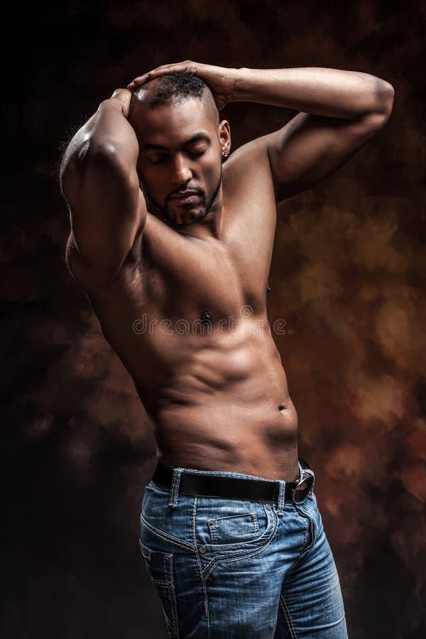 Naken man med den perfekta kroppen som poserar i jeans royaltyfria foton