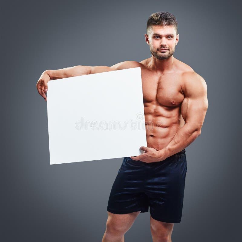 Naken muskulös manbeläggning med ett baner royaltyfri fotografi