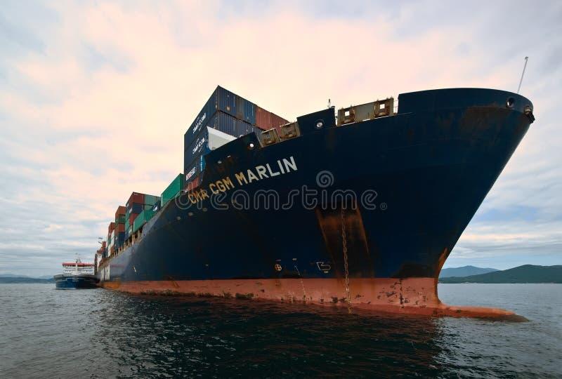 Nakhodka Rússia - 2 de agosto de 2015: Petroleiro Zaliv Nakhodka de Bunkering um grande espadim da CGM de CMA do navio de recipie imagem de stock