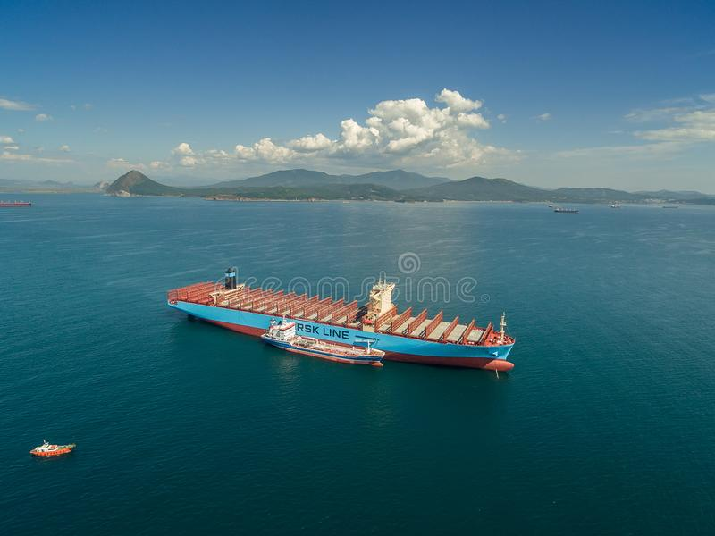 Nakhodka Rússia - 7 de setembro de 2017: Petroleiro Zaliv Nakhodka de Bunkering um grande navio de recipiente Maersk Honam imagens de stock royalty free