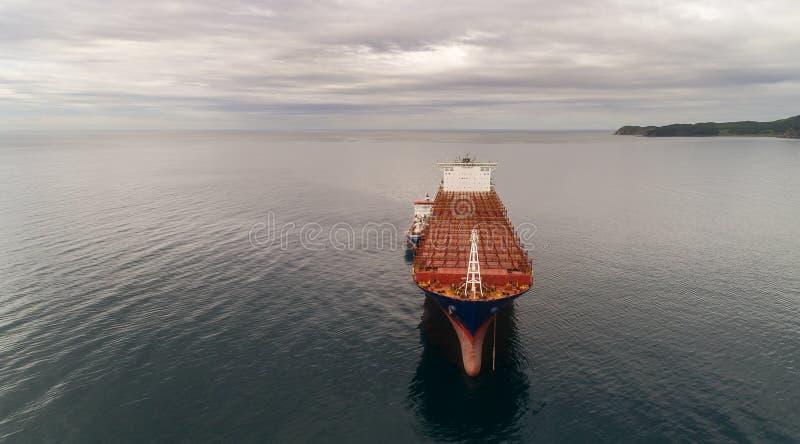 Nakhodka Ryssland - den 11 augusti 2017: bunkring tanker Zaliv Nakhodka ett stort containerfartyg APL Paris royaltyfri fotografi
