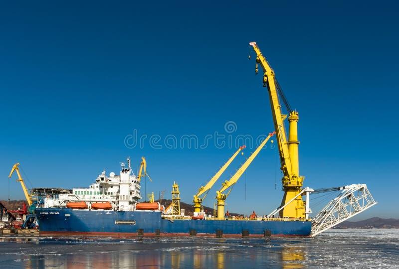 Nakhodka, Ryssland - 12 januari 2019: Kärnvärppningsfartyg för kranning (Academic Chersky) som ligger i hamnen vid piren royaltyfri foto