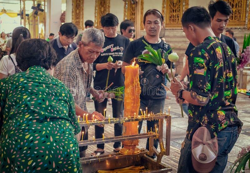NAKHON PATHOM, ΤΑΪΛΆΝΔΗ - 25 ΑΥΓΟΎΣΤΟΥ: Τοπικός βουδιστικός προετοιμάζει τα κεριά για να ανάψει το θυμίαμα για την επίκληση στο β στοκ εικόνες