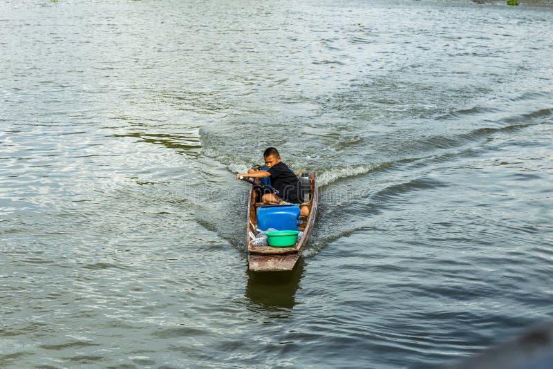 Nakhon Pathom, Tajlandia, Maj/- 26 2018: Chłopiec przejażdżka motorowa łódź, dziecko zręcznie kontroluje motorboat w rzece fotografia stock