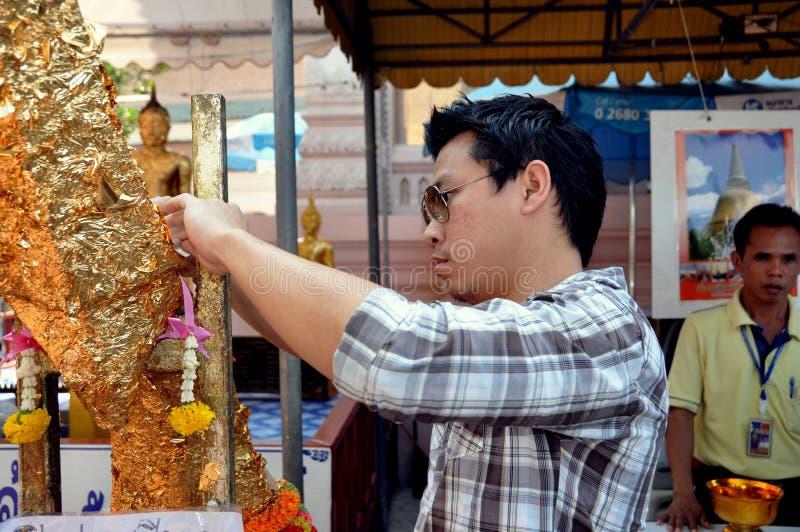 Nakhon Pathom, Thailand: Mann, der Goldblatt an Buddha anwendet stockfotografie