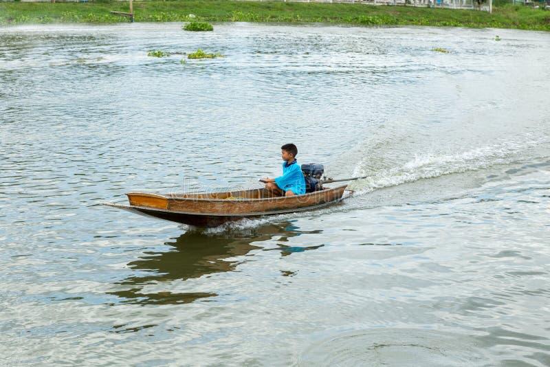 Nakhon Pathom/Thailand - Mei 26 2018: De jongensaandrijving een motorboot, kind controleert skillfully een motorboot in de rivier stock foto
